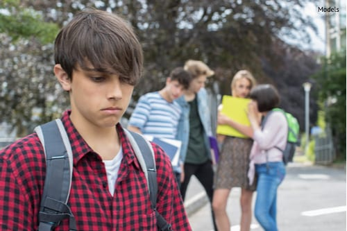 unhappy boy being gossiped about by school friends-img-blog