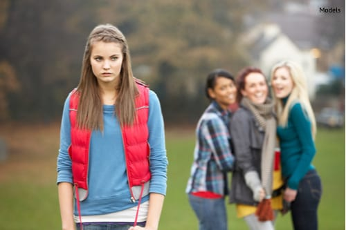 upset teenage girl with friends gossiping in background-img-blog