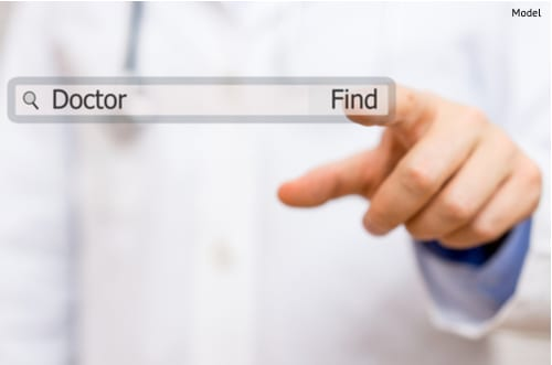 Doctor clicking 'find' when searching online for a doctor.