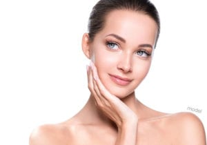 A woman enjoying her defined facial contours that is free of wrinkles, sagging, and jowls, due to her facelift procedure.